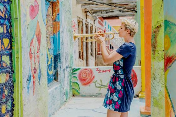A woman plays trumpet in the Pietermaai District of Willemstad